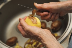 Elderly woman to peel potatoes. Kitchen working. Prepare food