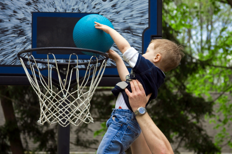 A small child being held up to slam dunk a basketball